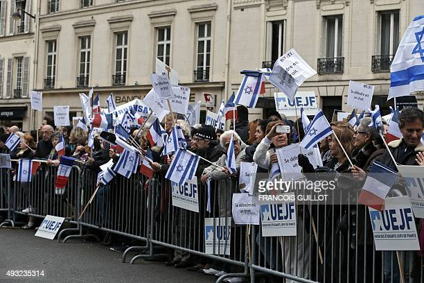 People listen to a speech by the President of the French Union of Jewish Students during a gathering called by the UEJF outside the Israeli embassy...