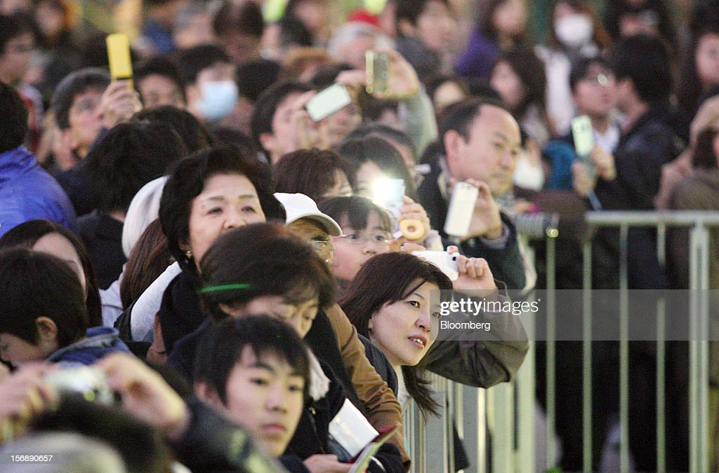 People listen to a speech by Yoshihiko Noda, Japan's prime minister and president of the Democratic Party of Japan (DPJ), unseen, during a campaign rally for the Dec. 16 general election in Kawasaki City, Kanagawa Prefecture, Japan, on Saturday, Nov. 24, 2012. The government taking office after Japan's Dec. 16 election will pick the central bank's top three jobs, a chance to reshape policy in the third-largest economy that the opposition aims to seize for unlimited stimulus. Photographer: Tomohiro Ohsumi/Bloomberg via Getty Images