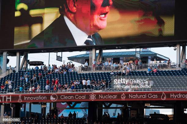 People listen to a video from US President Donald Trump during the Congressional Baseball Game between Democrats and Republicans at Nationals Stadium...