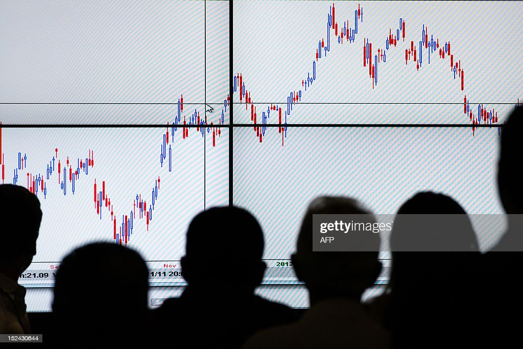 People listen to an explanation of the stock chart during the Expo Money in Sao Paulo, Brazil, on September 20, 2012. The Expo Money became the largest event of financial education and investment in Latin America since 2002 and today the annual expo covers 13 Brazilian cities. AFP PHOTO/Yasuyoshi CHIBA