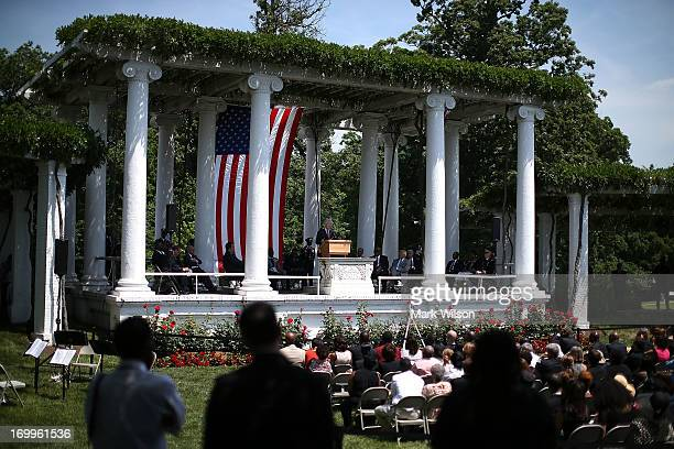 People listen to former US Preseident Bill Clinton speak during a ceremony to honor civil rights pioneer Medgar Evers at an Arlington National...