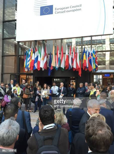 People listen to instructions after being evacuated from the European Council Europa building after a technical incident in Brussels on October 18...