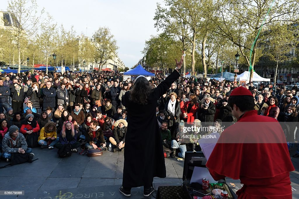 People listen to members of the group 'Eglise de la Tres Sainte Consommation' (Church of the Very Blessed Consumption) during a gathering of the 'Nuit Debout' (Up All Night) movement against the French government's proposed labour reforms at the Place de la Republique in Paris on April 30, 2016. / AFP / MIGUEL