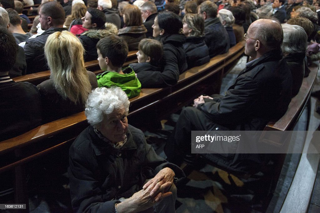 People listen to priests during a mass at the church of Sierre in Switzerland on March 13, 2013, commemorating the bus crash in Sierre a year ago. In the evening of March 13, 2012 a bus accident occurred in a tunnel in Sierre, Valais, Switzerland, killing 28 people, including 22 children, and injuring 24 others. The children from the Stekske primary school in Lommel and Sint-Lambertus school in Heverlee, in Belgium were on their way home from a ski vacation. HEGER