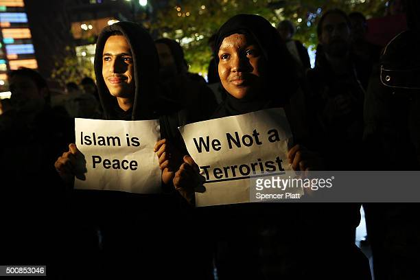 People listen to speakers at a demonstration against racism and conservative presidential candidate Donald Trump's recent remarks concerning Muslims...