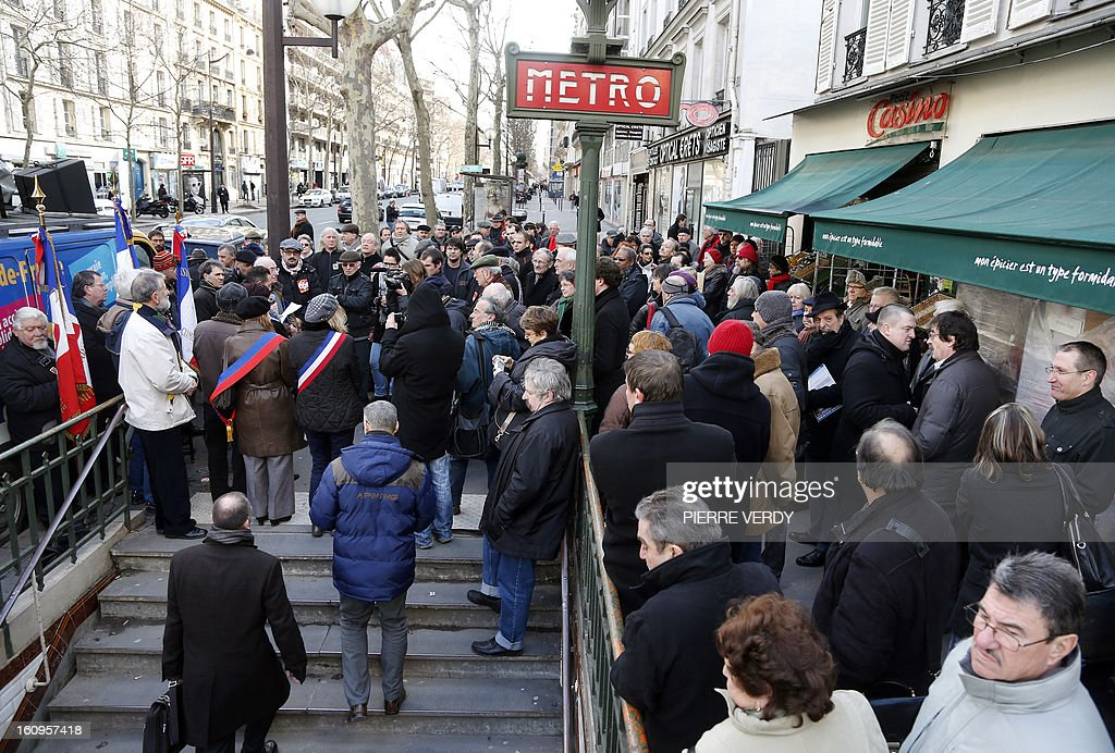 People listen to speeches on February 8, 2013 in Paris during a commemoration ceremony to mark the 51th anniversary of the February 8, 1962 killing by police of nine demonstrators at the Paris Charonne metro station during a peaceful, but outlawed demonstration which had seen some 30,000 people rally to call for peace in Algeria.