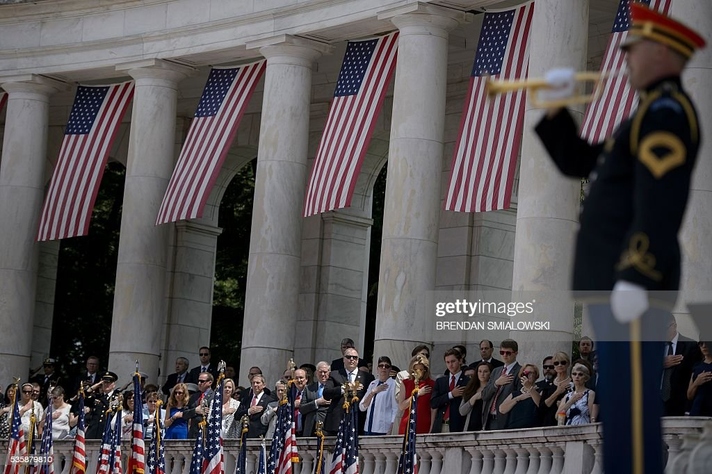 People listen to Taps during an event to honor Memorial Day at Arlington National Cemetery on May 30, 2016 in Arlington, Virginia. / AFP / Brendan Smialowski