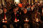 People listen to testimonials from the families of shooting victims at a conference and candlelight vigil as part of a National Day of Outrage in New...