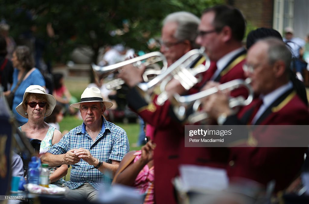 People listen to the Cobham Brass Band playing in College Garden in the grounds of Westminster Abbey on July 24, 2013 in London, England. A series of lunchtime concerts entitled 'Brass on the Grass' are being held between July 24 and August 28, 2013.