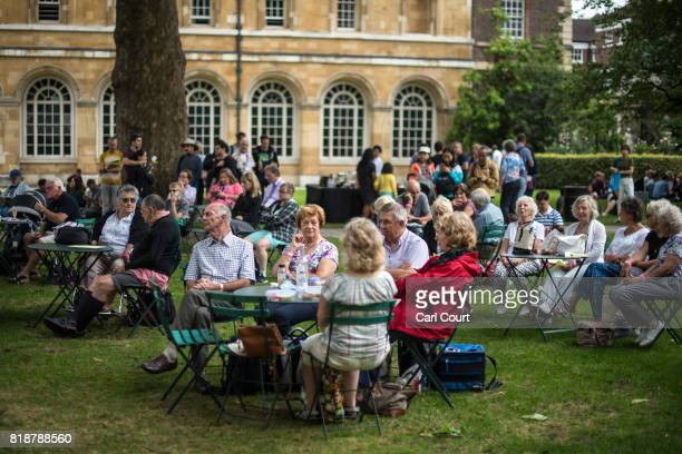 People listen to the Cobham Brass Band playing in College Garden in the grounds of Westminster Abbey on July 19 2017 in London England A series of...