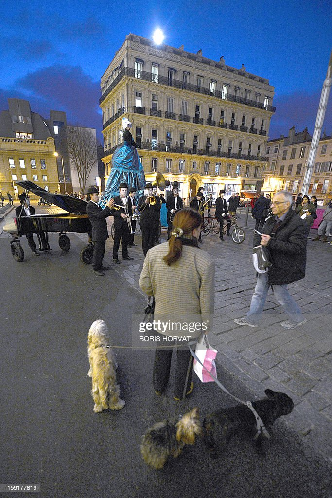 People listen to the French band 'La Rumeur' performing during the presentation of a new stamp's effigy published by French postal services La Poste and displayed on the facade of the regional prefecture in Marseille, southern France, ahead of the 2013 'Marseille-Provence European Capital of Culture', starting on January 12.