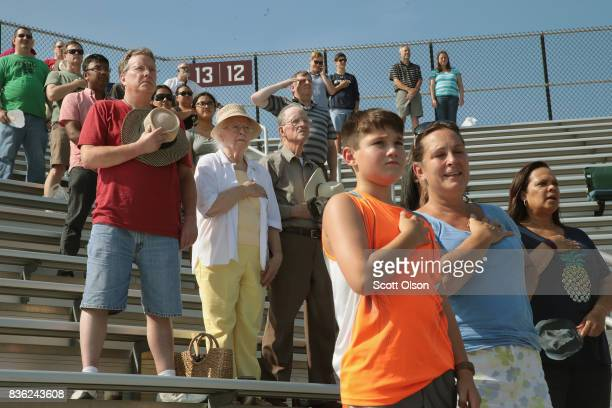 People listen to the national anthem at the start of festivities at Saluki Stadium on the campus of Southern Illinois University for the solar...