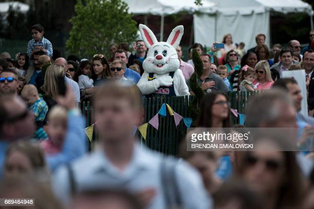 People listen to the US national anthem during the Easter Egg Roll on the South Lawn of the White House April 17 2017 in Washington DC / AFP PHOTO /...