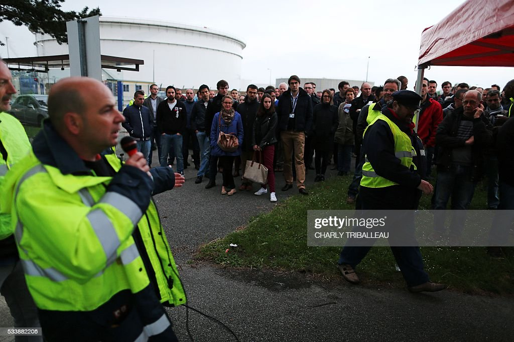 People listen to unionists who called for a strike, nearby the ExxonMobil oil refinery in Notre-Dame-de-Gravenchon, northwestern France, on May 24, 2016, following blockades of several oil refineries and fuel depots in France by protesters opposed to government labour reforms. The morning teams of the ExxonMobil oil refinery in Notre-Dame-de-Gravenchon, France's second largest refinery, seemed to ignore a strike called by the Force Ouvriere (FO) and General Confederation of Labour (CGT) French workers' unions on May 24. / AFP / CHARLY