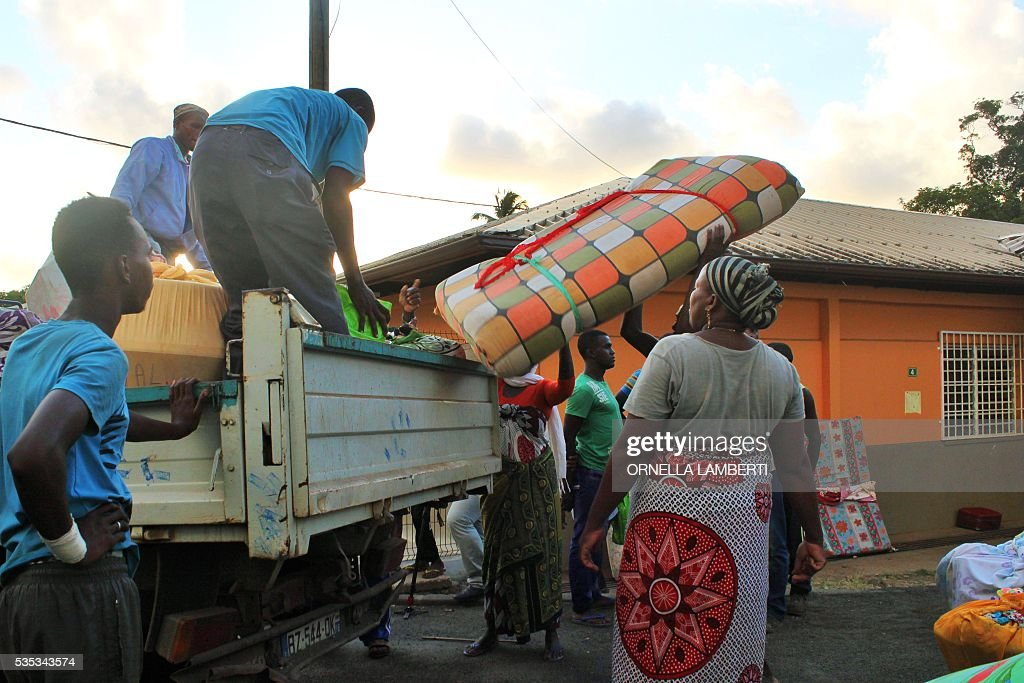 People load their belongings on a pick up on May 29, 2016 in Ouangani, center part of the French overseas region and department Mayotte, to go to the capital, Mamoutzou. Around 500 'illegal immigants', mostly from Comoros, evicted from their house by local Mayotte inhabitants, camp out since May 15, 2016 on Republique square at Mamoudzou as associations try to rehouse them. Rising anti-migrant anger has seen groups of up to 100 men gather in villages with lists of houses belonging to foreigners and going from door to door forcing them to leave. Police have tried to prevent violence, but have been unable to stop the pressure mounting on foreigners -- including many who are living on Mayotte legally -- who have fled their homes in fear. Mayotte opted to remain under French rule when the other islands in the Comoros archipelago chose independence in 1975. / AFP / ORNELLA