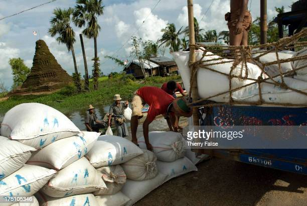 People load up a truck with rice bags for survivors of cyclone Nargis who have settled along the road from Pyapon to Bogale According to official...