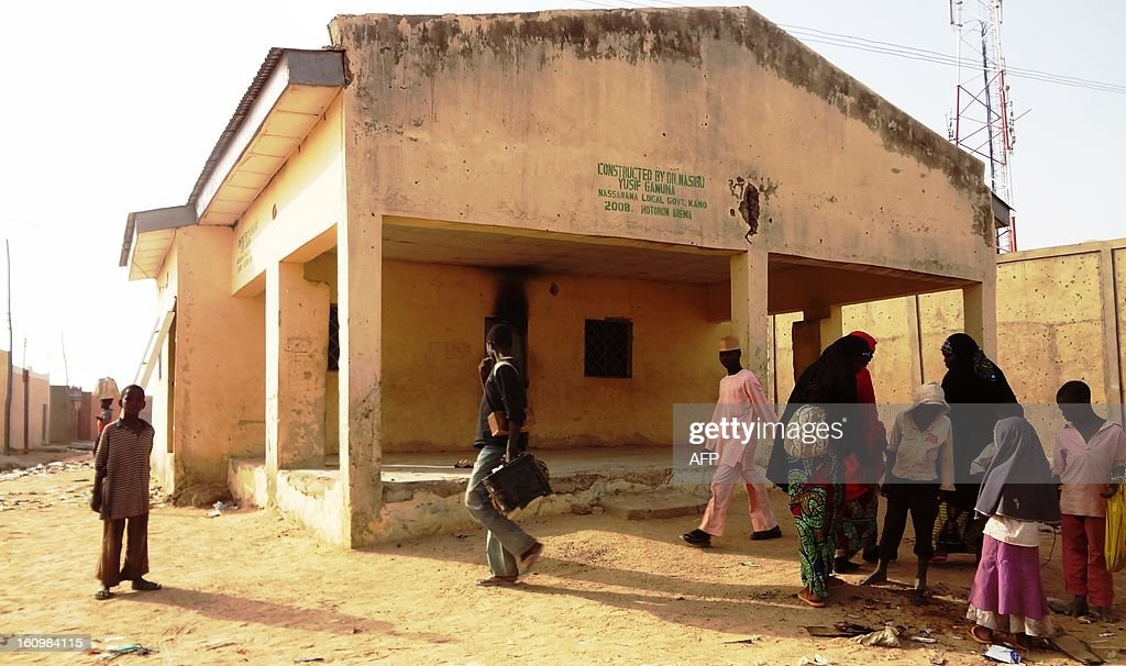 People loiter around the Haye dispensary on February 8, 2013 in the northern Nigerian city of Kano, where gunmen on motorised tricycle killed seven female polio immunisation workers. Ten polio immunisation workers, nine of them women, were killed and five others injured in separate gun attacks on two polio clinics in the city. AFP PHOTO / Aminu ABUBAKAR