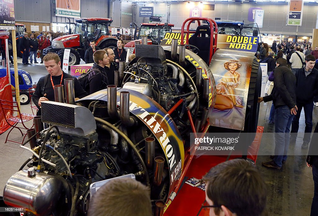 People look a 'tuned' 6000 horsepower tractor at the Paris International Agri-business Show (SIMA), which is part of the yearly International Agriculture Fair of Paris, on February 24, 2013, in Villepinte, a Paris suburb. The events runs from February 23 to March 3, 2013. AFP PHOTO / PATRICK KOVARIK
