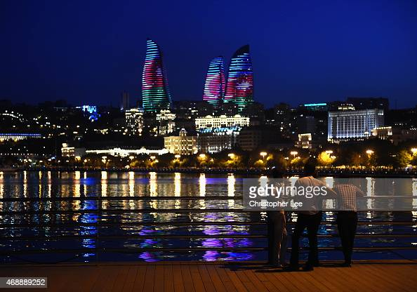 People look across the water as The Flame Towers are lit up at night on August 6 2014 in Baku Azerbaijan