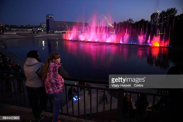 "People look across water to Vinnytsia Fountain ""Roshen"" near the factory on June 19 2016 in Vinnytsia Ukraine This is the only one multimedia..."