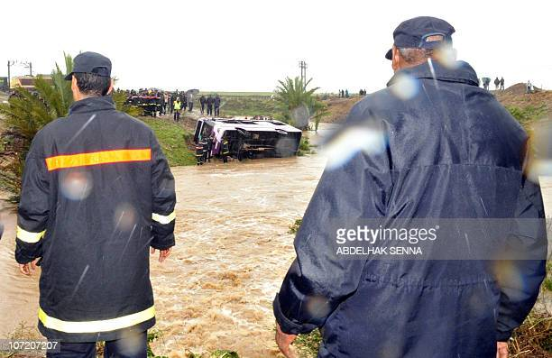 People look as firefighters attempt to lift a bus that plunged off a road into a ravine during heavy rain in Bouznika near Rabat on November 30 2010...