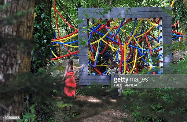 People look at a 3D abstract painting by the FrenchSerbian artist Igor Antic intitled 'Allochtone' in Mellionnec western France on June 13 as part of...