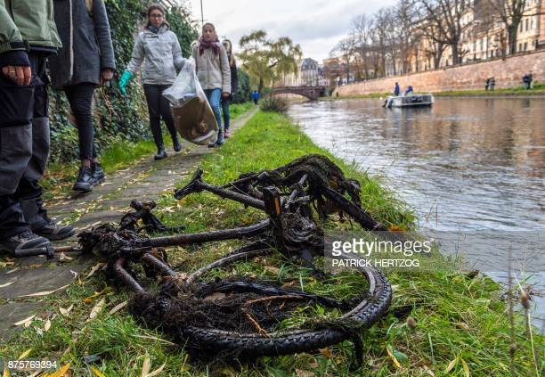 People look at a bike that was pulled out from the Ill river during a cleanup mission on its banks in Strasbourg eastern France on November 18 2017...