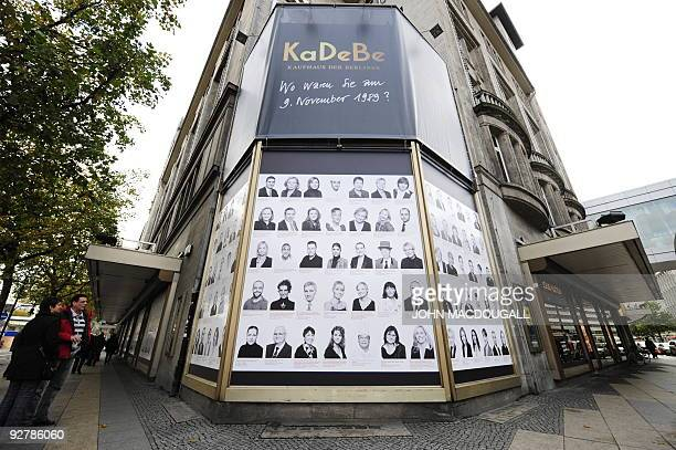 People look at a billboard featuring portraits of people and their recollections of the fall of the Berlin wall in 1989 at Berlin's KaDeWe department...