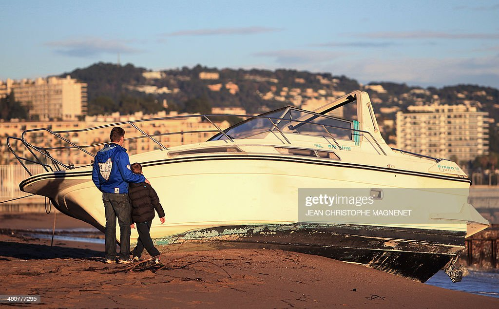 People look at a boat on January 5, 2014 which washed ashore on a beach in Cannes, southeastern France, after the area was hit by gale-force winds and pounding rain.