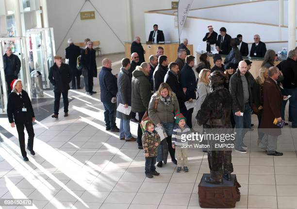 People look at a bronze Santa human statue in the entrance foyer at Sandown Park Racecourse