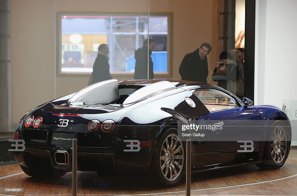People look at a Bugatti Veyron on display at a Volkswagen Group showroom on January 14, 2013 in Berlin, Germany. Volkswagen Group, which includes the VW, Audi, Porsche, Skoda, SEAT, Bentley and Bugatti brands, delivered a record 9.07 million cars to customers in 2012. Rising sales in the Americas and Asia helped to offset a drop in sales in western Europe.