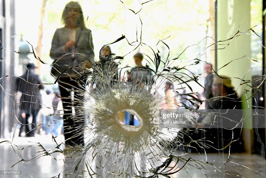 People look at a bullet hole in a window near to the Marks and Spencer on the Champs Elysees in Paris following yesterday's shooting of a police officer on April 21 2017. One police officer was killed and another wounded in a shooting on Paris's Champs Elysees, police said just days ahead of France's presidential election. France's interior ministry said the attacker was killed in the incident on the world famous boulevard that is popular with tourists.