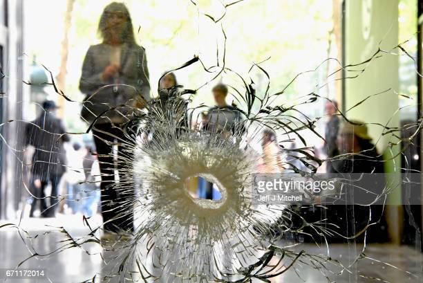 People look at a bullet hole in a window near to the Marks and Spencer on the Champs Elysees in Paris following yesterday's shooting of a police...
