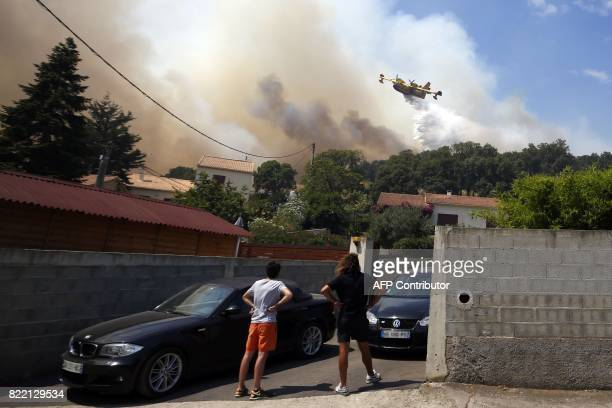 People look at a Canadair aircraft dropping water over a fire on July 25 in Ortale de Biguglia near Biguglia on the French Mediterranean island of...