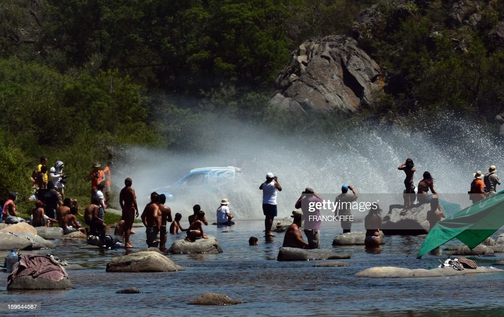 People look at a car during the Stage 10 of the Dakar 2013 between Cordoba and La Rioja, Argentina, on January 15, 2013. The rally takes place in Peru, Argentina and Chile between January 5 and 20. AFP PHOTO / FRANCK FIFE