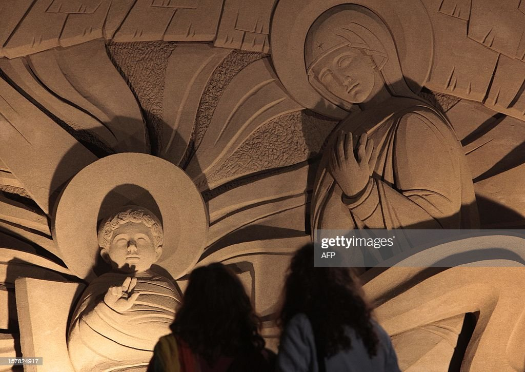 People look at a Christmas nativity scene made from sand at the international beach resort of Las Canteras, in Las Palmas de Gran Canaria on the Spanish Canary island of Gran Canaria on December 6, 2012. Artist from nine countries recreated the scenes depicting the birth of Jesus of Nazareth. AFP PHOTO/ DESIREE MARTIN