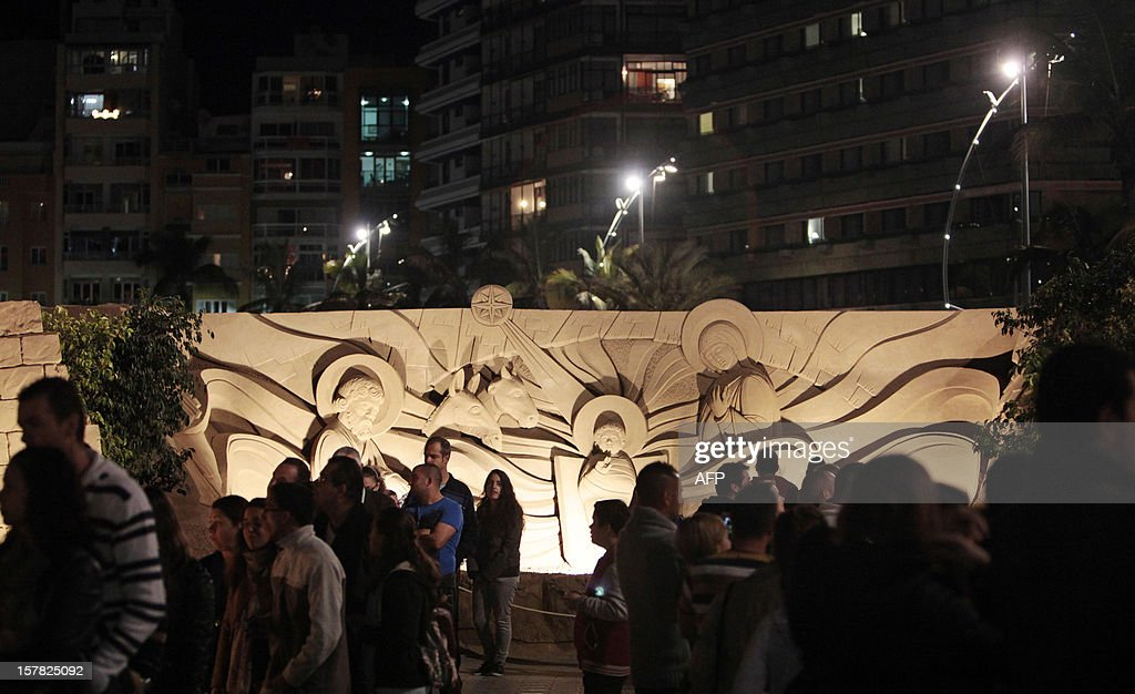 People look at a Christmas nativity scene made from sand at the international beach resort of Las Canteras, in Las Palmas de Gran Canaria on the Spanish Canary island of Gran Canaria on December 6, 2012. Artist from nine countries recreated the scenes depicting the birth of Jesus of Nazareth.