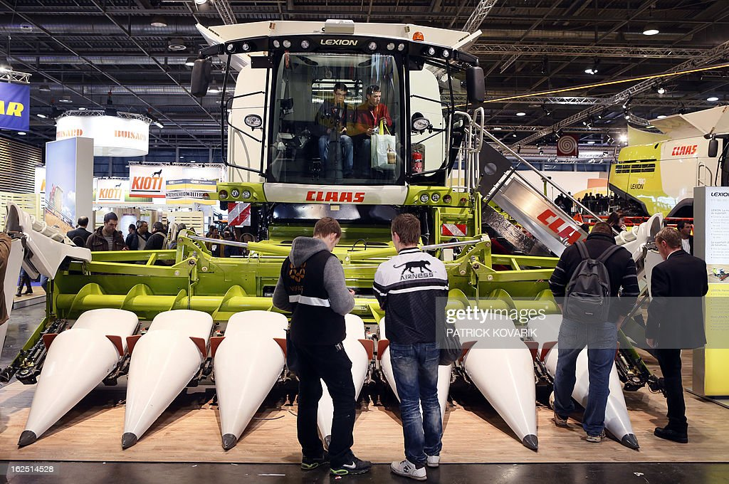People look at a 'Claas' corn harvester at the Paris International Agri-business Show (SIMA), which is part of the yearly International Agriculture Fair of Paris, on February 24, 2013, in Villepinte, a Paris suburb. The events runs from February 23 to March 3, 2013.