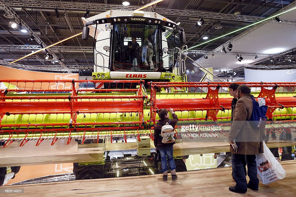 People look at a 'Claas' harvester at the Paris International Agri-business Show (SIMA), which is part of the yearly International Agriculture Fair of Paris, on February 24, 2013, in Villepinte, a Paris suburb. The events runs from February 23 to March 3, 2013.