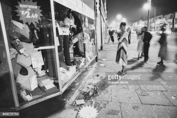 People look at a clothing shop's window damaged during the National Front meeting at Boulton Road Ladywood Birmingham UK 16th August 1977