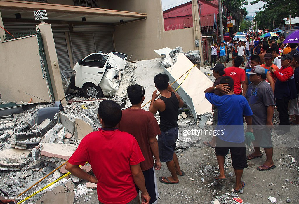 People look at a collapsed building in Cebu City, Philippines after a major 7.1 magnitude earthquake struck the region on October 15, 2013. At least 20 people were killed on October 15 when the earthquake tore down buildings across three islands that are among the Philippines' most popular tourist attractions, authorities said. AFP PHOTO / Chester Baldicantos