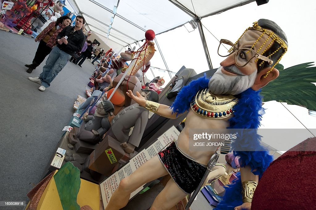People look at a Falla, a gigantic sculpted structure of cardboard and wood which humorously portrays relevant current events and personalities, caricaturing Spain's Prime Minister Mariano Rajoy during an exhibition before preparations for the Fallas Festival, in Valencia on March 11, 2013. The Fallas will be burned in the streets of Valencia on March 19, 2013, as a tribute to St. Joseph, patron saint of the carpenters' guild.