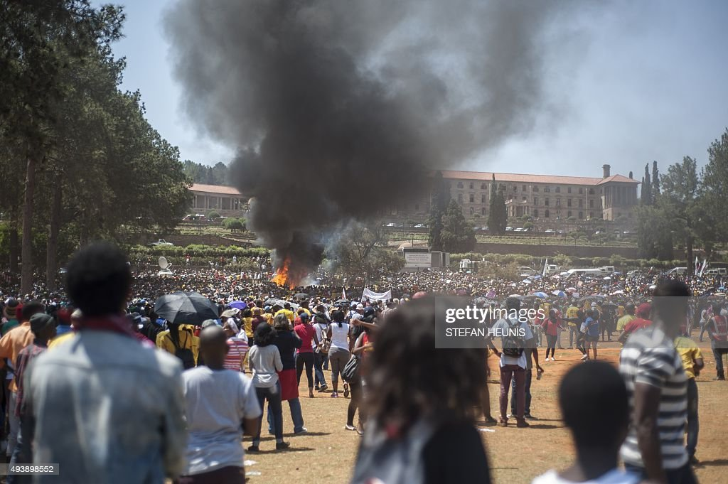 People look at a fire started by protestors during a student demonstration in front of the Union Buildings the seat of the government in Pretoria on...