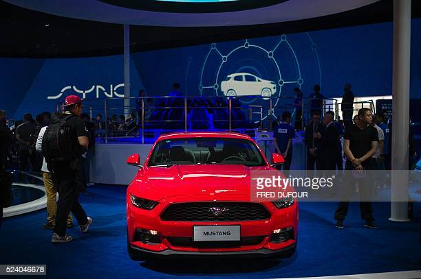 People look at a Ford Mustang on display at the Beijing Auto Show in Beijing on April 25 2016 Global carmakers gathered in Beijing on April 25 to...