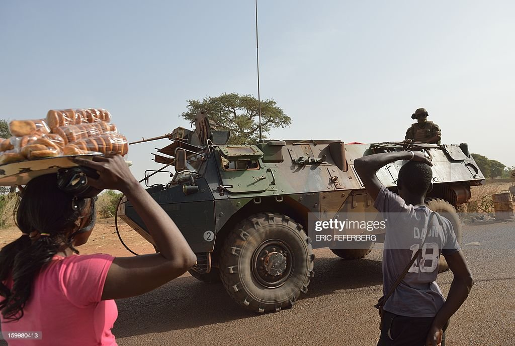 People look at a French armoured vehicle part of a big convoy coming from Bamako and going to Daibali (400km north of Bamako) on January 24, 2013 in Segou. Paris sent in its forces on January 11 to rescue Mali from Al Qaeda-linked groups controlling the north.