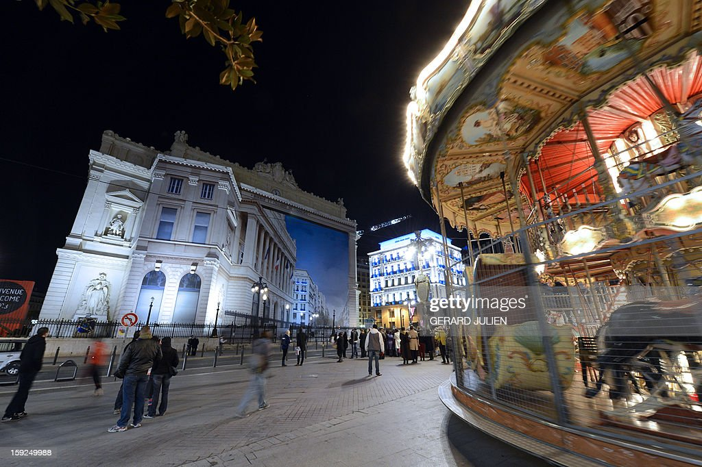 People look at a giant trompe-l'oeil mural by artist Pierre Delavie set up on the facade of the Palais de la Bourse building in Marseille on January 10, 2013, as part of the many cultural events taking place in Marseille in relation to the city being named 2013 European 'capital of culture'. On January 12, the city will be named 'capital of culture' which will kick off a range of exhibitions and events.