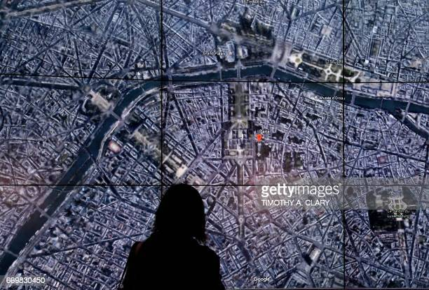 People look at a Google Earth map of ParisFrance on a screen as Google Earth unveils the revamped version of the application April 18 2017 at a event...