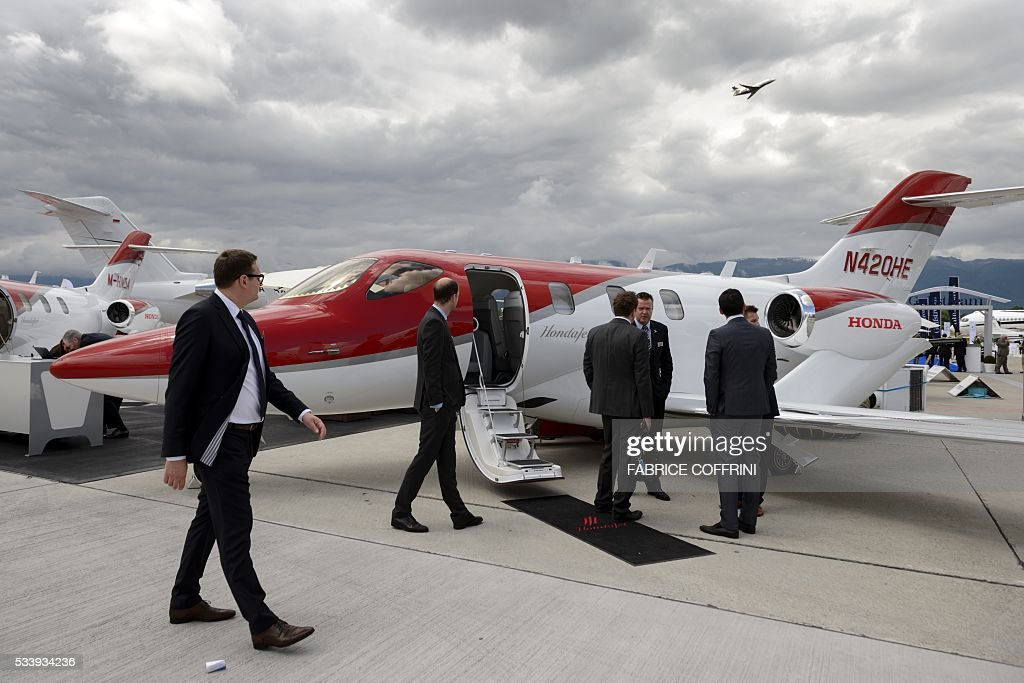 People look at a HondaJet at the static stand of Japanese plane maker Honda Corporate Jet Aircraft during the European Business Aviation Convention & Exhibition (EBACE) on May 24, 2016 in Geneva. / AFP / FABRICE