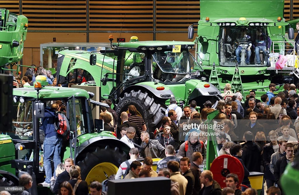 People look at a 'John Deere' agricultural machines at the Paris International Agri-business Show (SIMA), which is part of the yearly International Agriculture Fair of Paris, on February 24, 2013, in Villepinte, a Paris suburb. The events runs from February 23 to March 3, 2013.