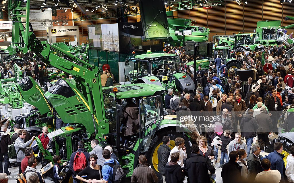 People look at a 'John Deere' agricultural machines at the Paris International Agri-business Show (SIMA), which is part of the yearly International Agriculture Fair of Paris, on February 24, 2013, in Villepinte, a Paris suburb. The events runs from February 23 to March 3, 2013. AFP PHOTO / PATRICK KOVARIK